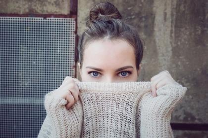 服で顔を隠す女性