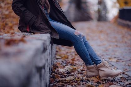 デニムパンツをはいて道端に座る女性