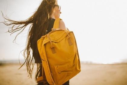 黄色いリュックを背負った女性