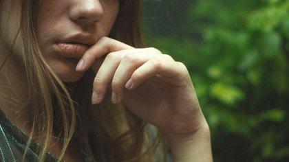 口元を手で触れる女性画像