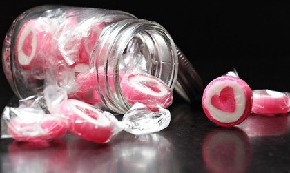 ハートのキャンディを瓶から出している画像