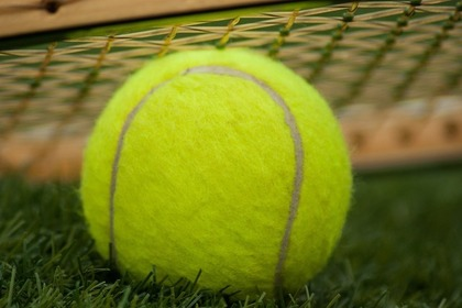 テニスボールと上に乗せられたラケット