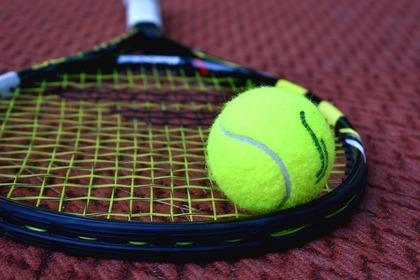 ラケットの上に乗った硬式テニスボール