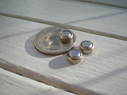 コインと一緒に置かれた3つのボタン電池
