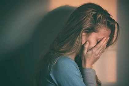 顔を手で覆って落ち込んでいる女性