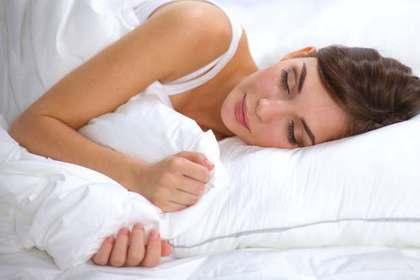 白い寝具に包まれ眠る女性画像