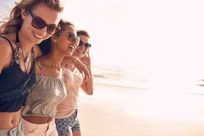 浜辺で3人の美女が笑っている