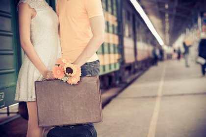 旅行鞄を手に寄り添う男女