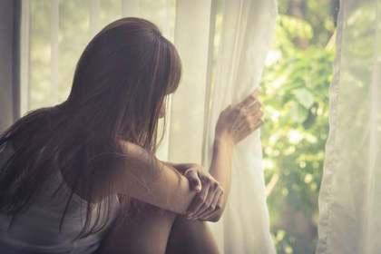 窓越しに外を見る女性