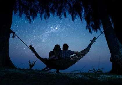 ハンモックから星を眺めるカップル