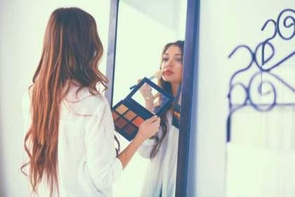 全身鏡で化粧をする女性