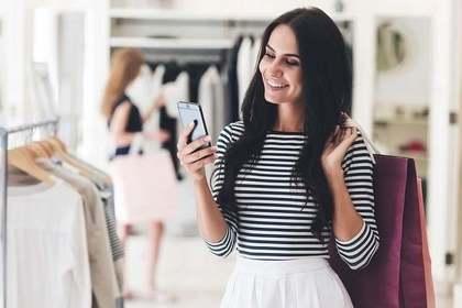 買い物中にスマホを見る女性