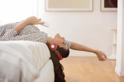 ベッドの上で音楽を聴く女性