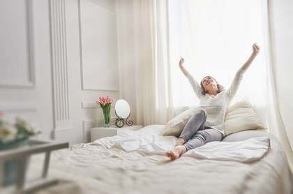 綺麗な部屋で腕を伸ばしている女性
