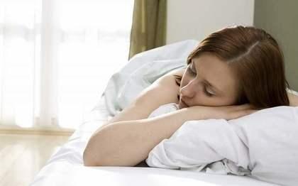 布団の中で寝る女性