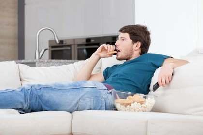 ソファーでお菓子を食べる男性