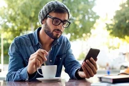 コーヒーを飲みながらスマホをいじる男性