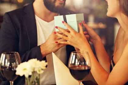 ワインを飲みながら女性にプレゼントを渡す男性画像