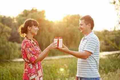 女性にプレゼントを渡す男性画像
