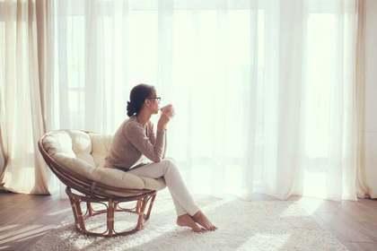 椅子に座って窓の外を見る女性