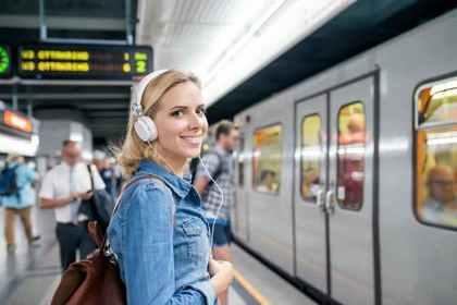 ヘッドホンをして電車に乗る女性