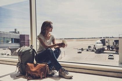 大きな荷物を持って休憩する女性