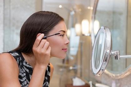鏡を見てマスカラを塗る女性