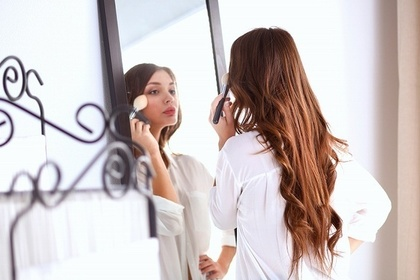 全身鏡でメイクをする女性
