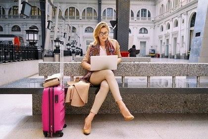 スーツケースを置いて検索する女性