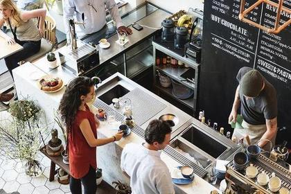 カフェのオープンキッチン前に立つ男女画像