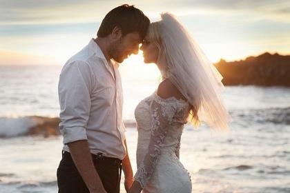 海をバックにウェディングドレスを着た男女