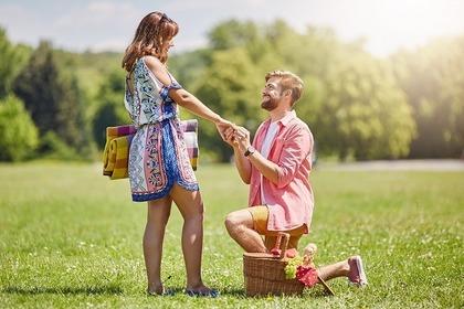 膝をつきプロポーズする男性