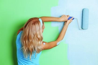 壁に色を塗る女性