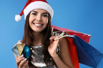 サンタ帽をかぶりプレゼントを持つ女性画像