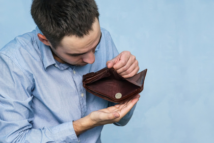 空っぽの財布を見る男性