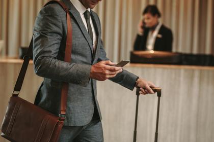 スーツケースとカバンを持ってスマホを触る男性