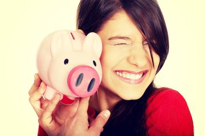 豚の貯金箱と笑顔の女性