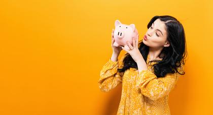 豚の貯金箱を見る女性