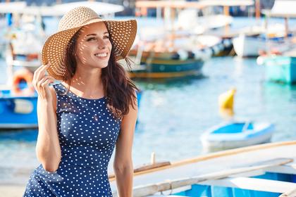 帽子を被って遠くを眺める女性