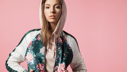ピンクの背景前のフードをかぶった女性画像