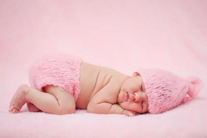 ピンクの毛糸のパンツを履いた赤ちゃん