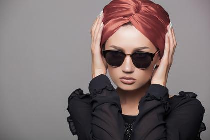 髪を押さえるサングラスの女性