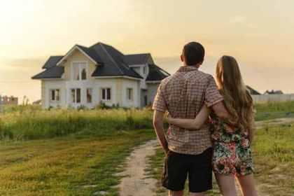 遠くの家を眺めてたたずむカップル