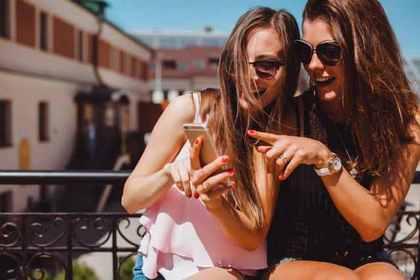ケータイをのぞき込むサングラスをかけた女性2人