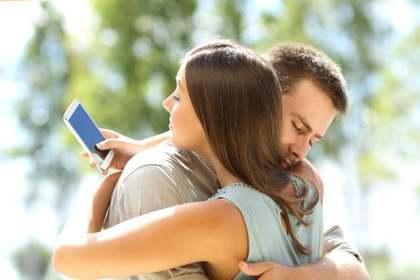 抱き合いながらスマホを見る女性