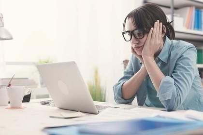 パソコンを見つめるメガネをかけた女性