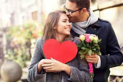 ハートを手にした女性のおでこにキスする男性