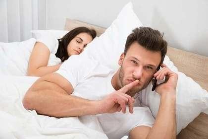 ベッドで電話をする男性