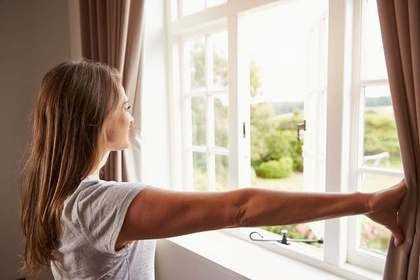 朝カーテンを開ける女性