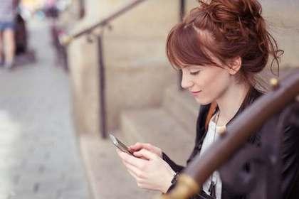 外で携帯を操作する女性